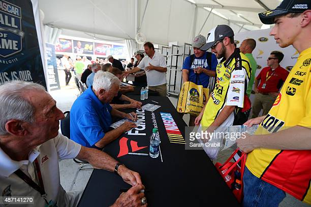Hall of Famers Ned Jarrett left and Junior Johnson second left sign their autographs for fans prior to the NASCAR Sprint Cup Series Bojangles'...