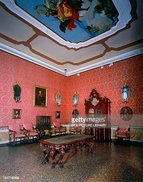 Hall of Tiepolo Ca' Rezzonico in the center a Venetian Baroque table with carved lion's claw legs late 17thearly 18th century against the wall a...