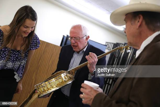 Halladay Quist shows US Sen Bernie Sanders a banjo as democratic US Congressional candidate Rob Quist looks on before the start of a campaign rally...