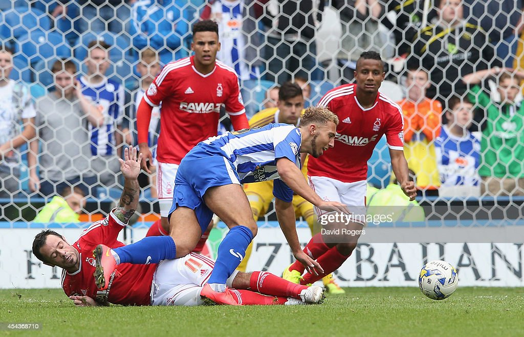 Hallam Hope of Sheffield Wednesday is brought down by Andy Reid on the edge of the penalty area during the Sky Bet Championship match between Sheffield Wednesday and Nottingham Forest at Hillsborough Stadium on August 30, 2014 in Sheffield, England.