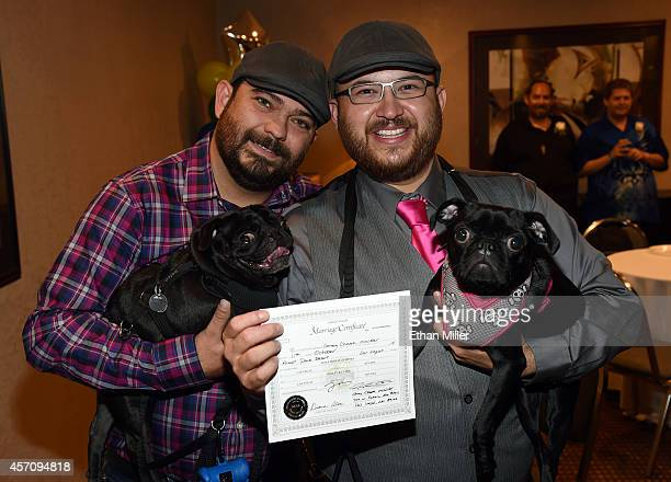 Halley Clark and Jes Cumpian both of Nevada hold their dogs Padfoot and Luna as they display their signed marriage certificate before getting married...