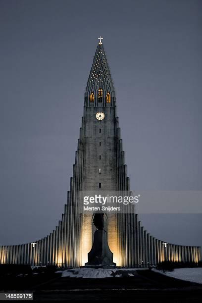 hallgrims church lit up in the evening, with leif eriksson statue in front. - merten snijders stockfoto's en -beelden