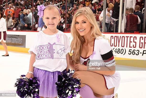 Hallie an Arizona Coyotes paw patrol member and Brookly who is currently fighting cancer pose for a picture during Hockey Fights Cancer night between...