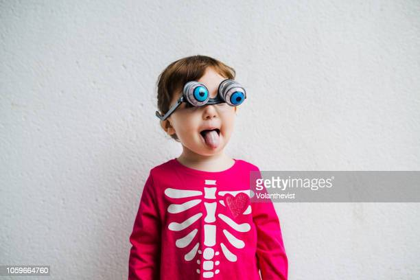 halloween baby girl wearing skeleton costume amb with fake horror eye glasses and tongue out - funny skeleton stock photos and pictures