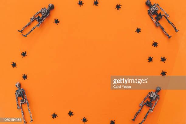 halloween background skeletons and spiders in orange