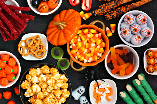 Halloween candy buffet table top view over a black background 1172823386