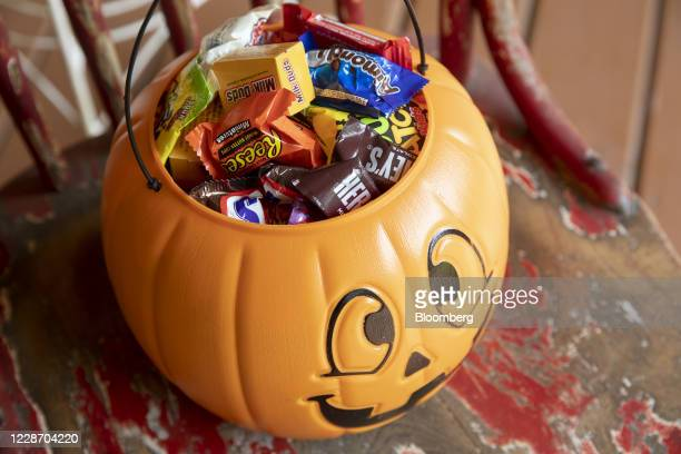 Halloween candy is displayed for a photograph inside a pumpkin themed treat bucket in Tiskilwa, Illinois, U.S., on Sunday, Sept. 20, 2020....
