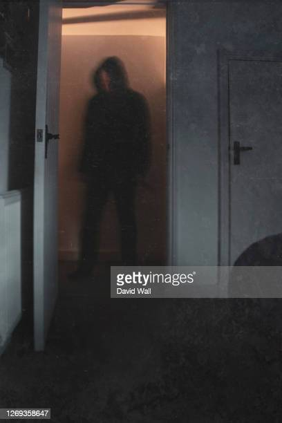 a halloween concept of a blurred scary, hooded figure, standing in a doorway. with a knife. with a vintage, abstract edit. - negative emotion stock pictures, royalty-free photos & images