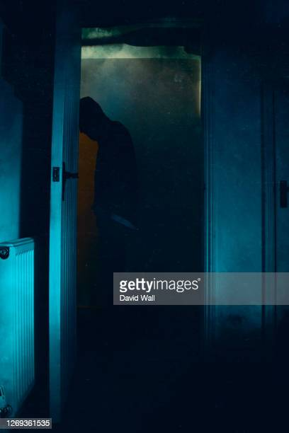 a halloween concept of a blurred scary, hooded figure, standing in a doorway. with a knife. with a vintage, abstract edit. - low stock pictures, royalty-free photos & images