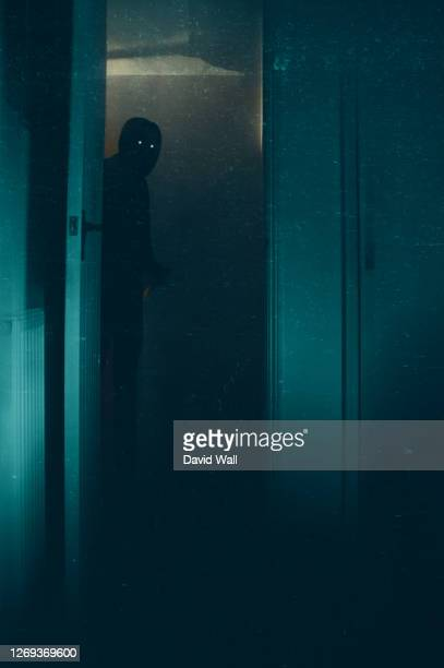 a halloween concept of a blurred scary, hooded figure, with glowing eyes. standing in a doorway. with a knife. with a vintage, abstract edit. - aparición acontecimiento fotografías e imágenes de stock
