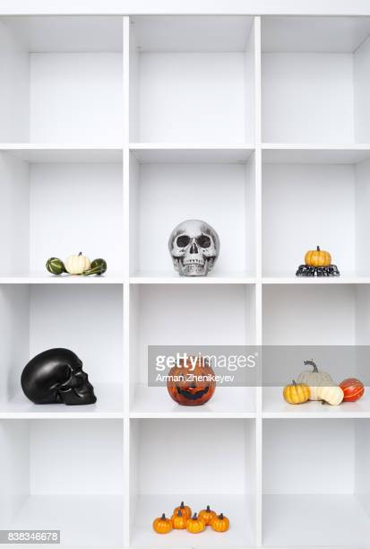 halloween decorations in bookshelf - ugly pumpkins stock photos and pictures