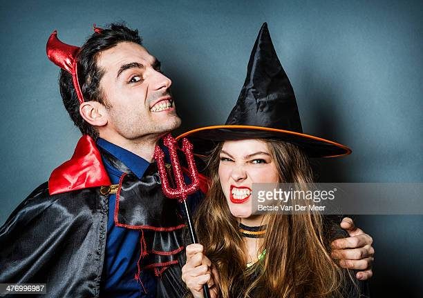 halloween devil and witch pulling faces. - devil costume stock photos and pictures