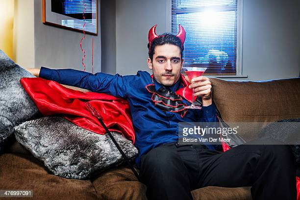 halloween devil relaxing on sofa with cocktail. - devil costume stockfoto's en -beelden