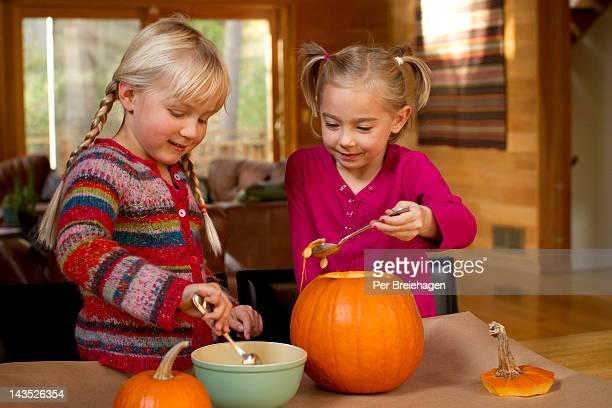 Halloween girls carving pumpkin