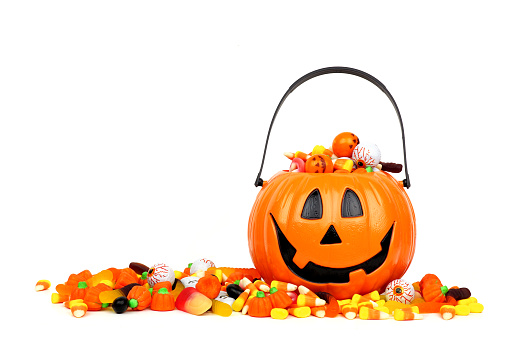 Halloween Jack o Lantern bucket filled with candy isolated on white 1174282589