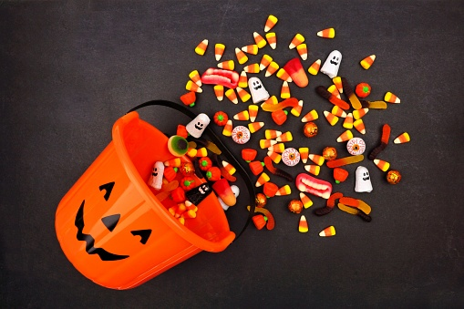 Halloween Jack o Lantern pail, top view with spilling candy 1032890422