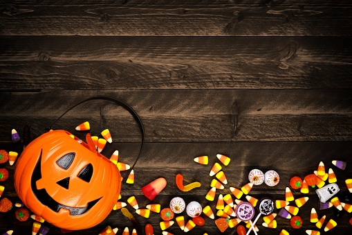 Halloween Jack o Lantern pail with bottom border of spilling candy over dark wood 1030150972