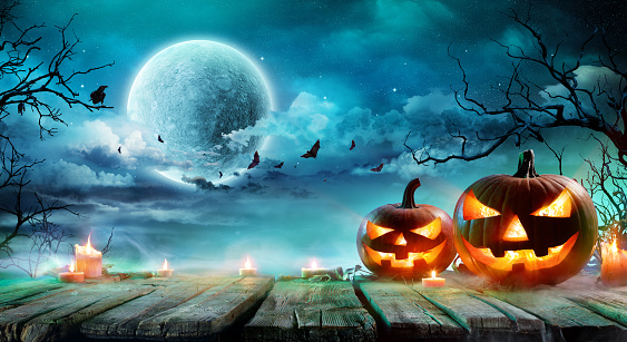 Halloween - Jack O' Lanterns And Candles On Table In Misty Night 1036034774