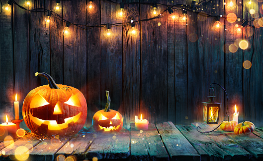Halloween - Jack O' Lanterns - Candles And String Lights On Wooden Table 1170764643