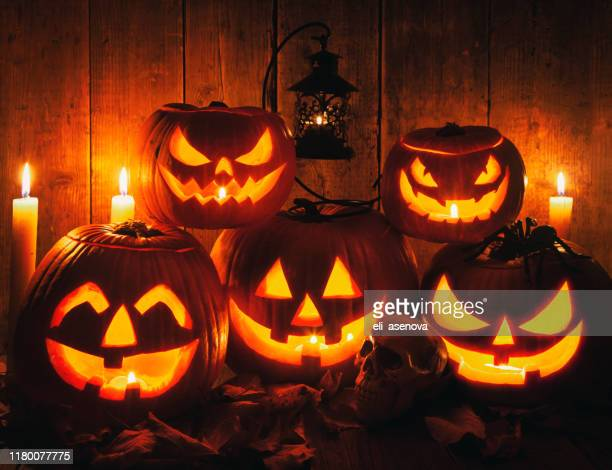 halloween jack-o-lantern pumpkins on rustic wooden background - halloween stock pictures, royalty-free photos & images