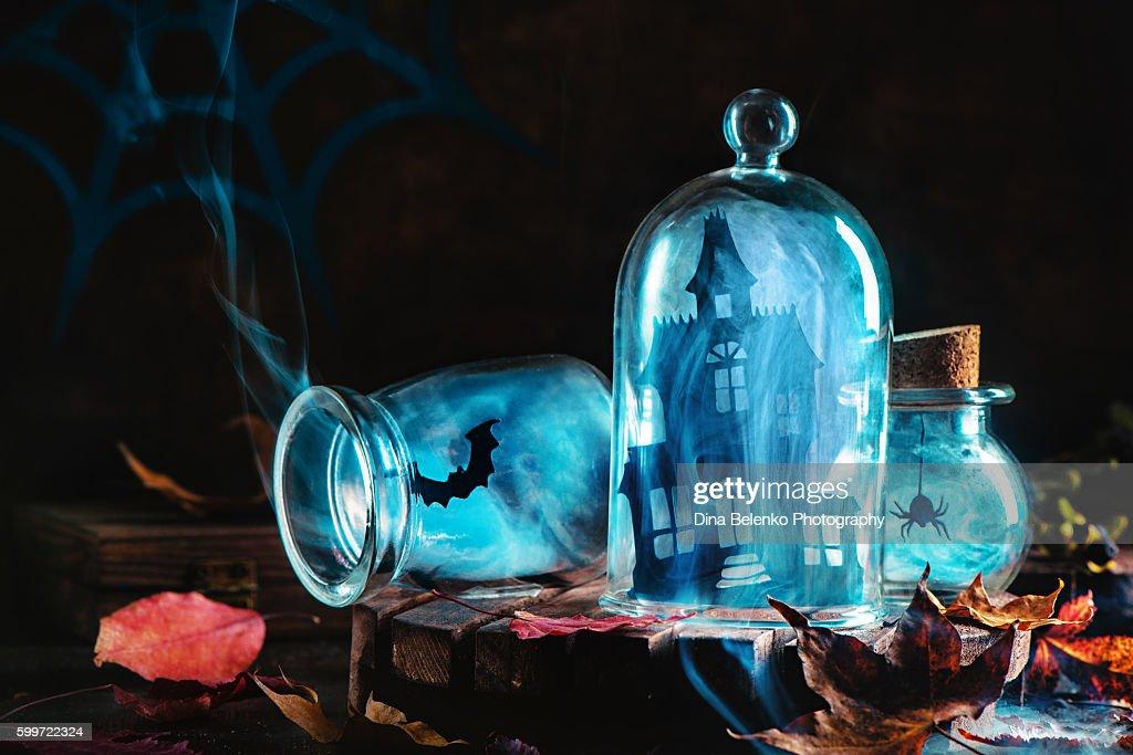 Halloween jars with smoke and haunred mansion : Stock Photo