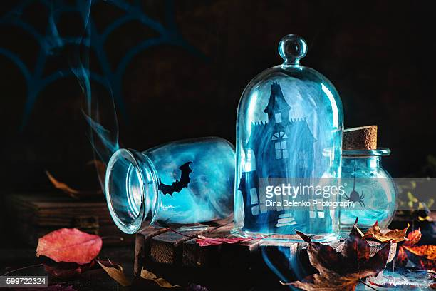 halloween jars with smoke and haunred mansion - halloween party stock photos and pictures