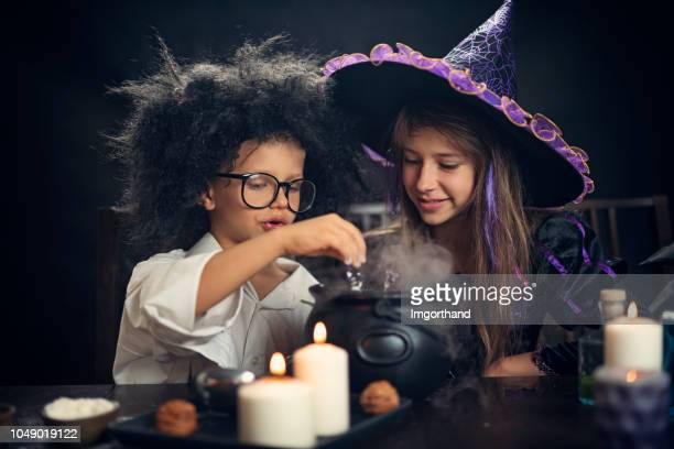 halloween kids playing with potions - naughty halloween stock photos and pictures