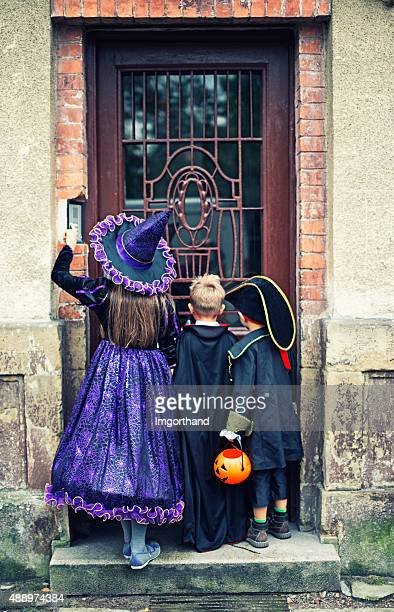halloween kids ringing the doorbell of an old scary house - doorbell stock pictures, royalty-free photos & images