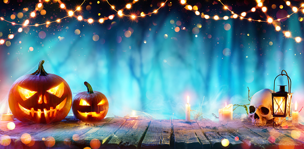 Halloween Party - Jack O' Lanterns And String Lights On Table In Misty Forest 1040369042