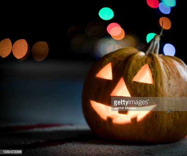 halloween pumpkin with blurred street lights - ugly wallpaper stock photos and pictures
