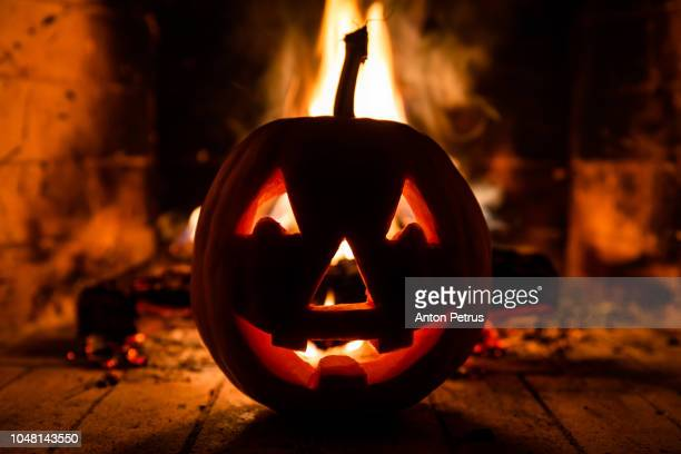 Halloween pumpkin with scary face on fire background
