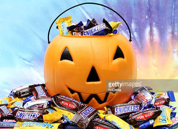 halloween pumpkin with trick or treat candy. - halloween candy stock photos and pictures