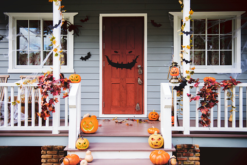 Halloween pumpkins and decorations outside a house 1058687260