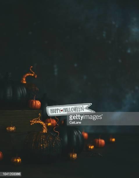 Halloween-Stillleben mit orange und schwarz glitzernden Kürbisse und Nachricht