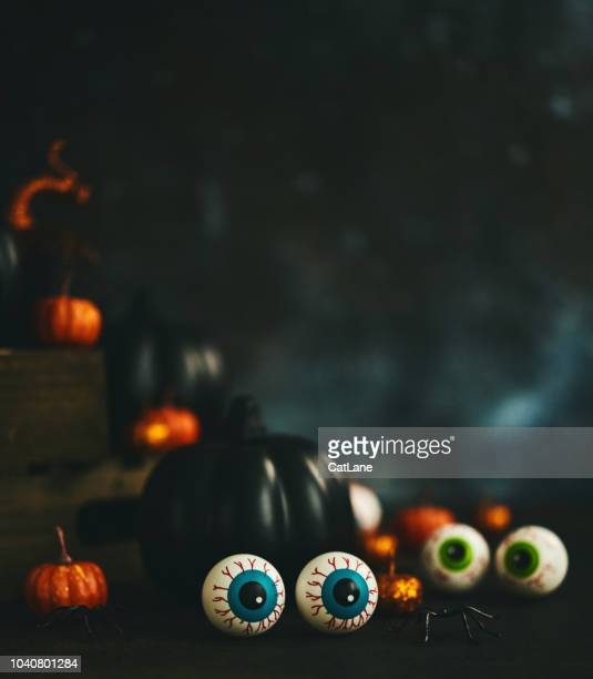 Halloween still life with orange and black glittery pumpkins, eyeballs and spiders