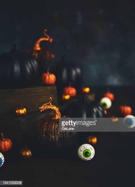 Halloween-Stillleben mit Orangen und schwarzen glitzernden Kürbisse, Augäpfel und Spinnen
