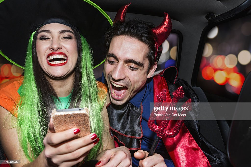 Halloween witch and devil laughing in back of car : Stock Photo