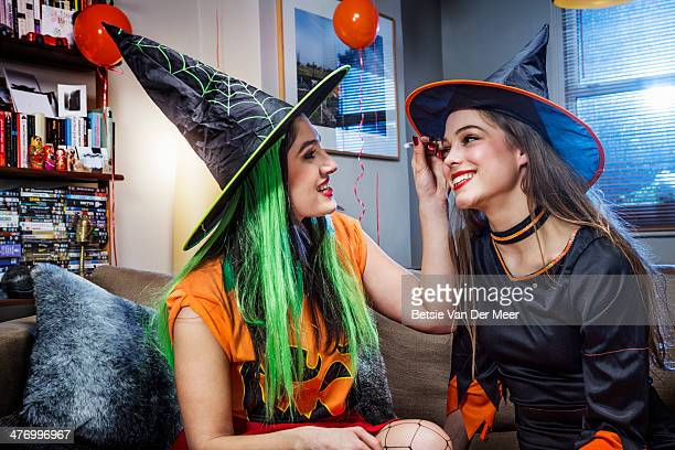 Halloween witch applying make up on friend.