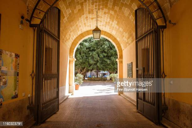 marsala, sicily, italy - ocober 17, 2019: hallway with a iron gate leading to a a park - finn bjurvoll stock pictures, royalty-free photos & images