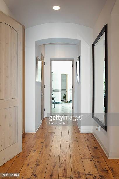 Hallway with mirror on wall in home