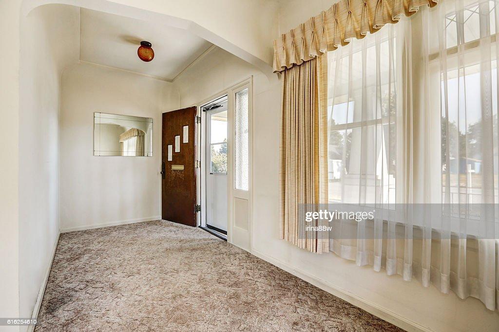 Hallway with view of opened front door and carpet floor : Foto de stock