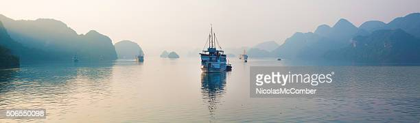 Halong Bay Vietnam panorama with tourist boats early dawn