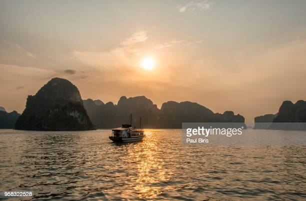 halong bay vietnam tourist ship with cliff island at sunset, vietnam - halong bay imagens e fotografias de stock