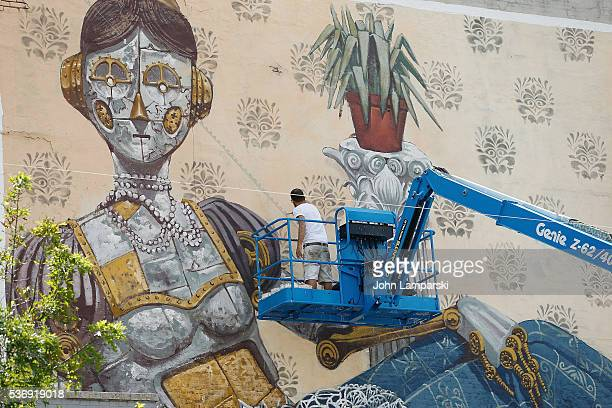 Halopigg and artist Pixel Pancho paint a mural in Chelsea on June 1 2016 in New York City