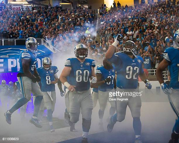 Haloti Ngata and Graham Glasgow of the Detroit Lions run onto the field to start the NFL game against the Tennessee Titans at Ford Field on September...