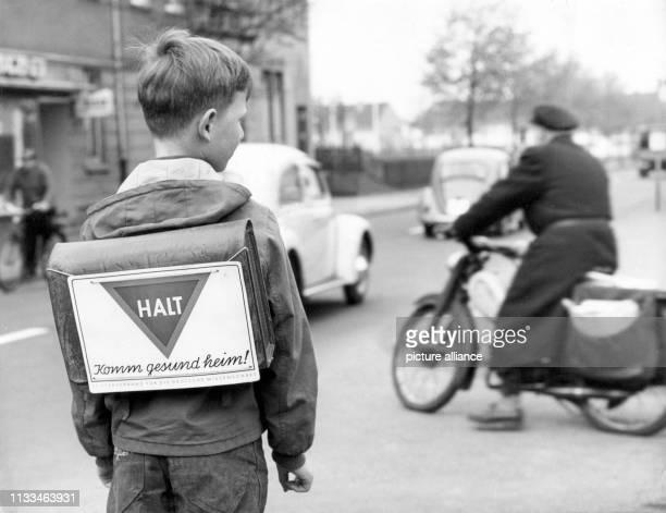 Halt und Komm gesund heim steht in großen Buchstaben auf dem Schultornister eines Erstklässers der 1960 in Essen auf dem Schulweg an einer von Autos...