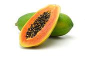 Halved and whole papaya fruits on white background
