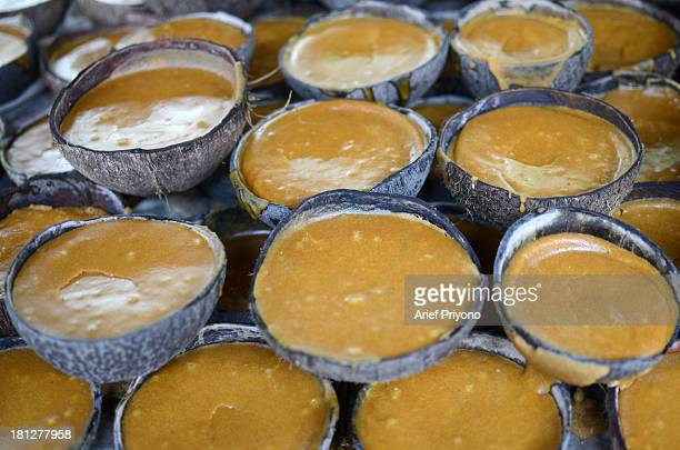 Halved coconuts make pots for setting brown sugar in a small factory in Slumbung Village Most Indonesian people use brown sugar to sweeten foods and...