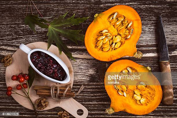 Halved fresh pumpkin on  rustic wooden table and cranberry sauce with knife and  cinnamon sticks