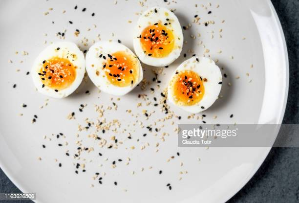 halved hard-boiled eggs on a plate - hard boiled eggs stock photos and pictures